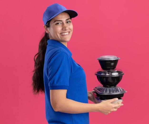Jovem entregadora sorrindo em pé na vista de perfil, usando uniforme com tampa segurando recipientes de comida isolados na parede rosa