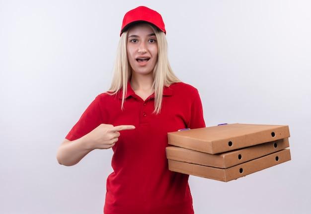 Jovem entregadora surpresa, vestindo camiseta vermelha e boné no aparelho dentário, aponta para a caixa de pizza na mão em fundo branco isolado