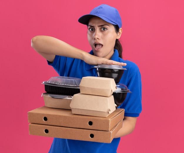 Jovem entregadora surpresa vestindo uniforme com tampa segurando recipientes de comida em caixas de pizza isoladas na parede rosa