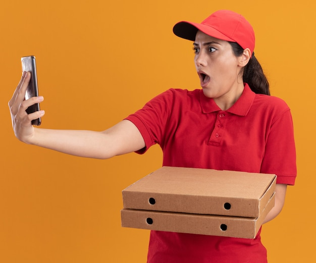 Jovem entregadora surpresa vestindo uniforme e boné segurando caixas de pizza e tirando uma selfie isolada na parede laranja