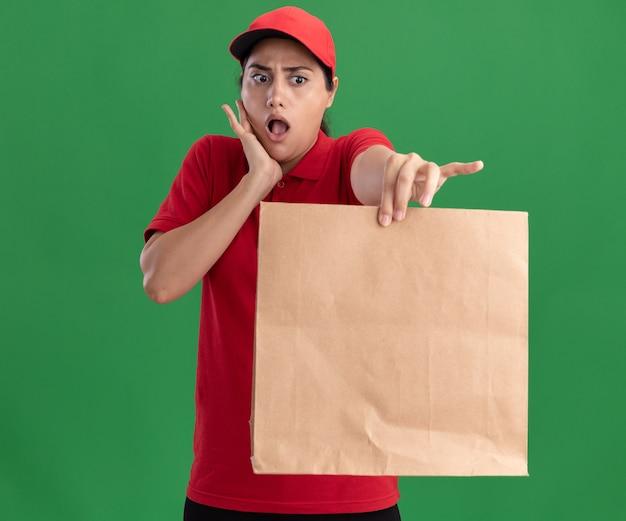 Jovem entregadora surpresa, vestindo uniforme e boné, segurando um pacote de comida de papel para a câmera, colocando a mão na bochecha isolada na parede verde