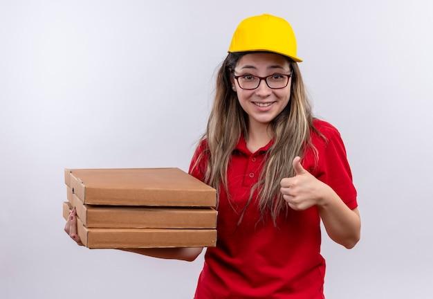 Jovem entregadora tímida de camisa polo vermelha e boné amarelo segurando uma pilha de caixas de pizza sorrindo e mostrando os polegares para cima