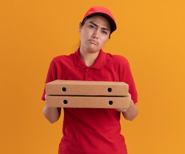 Jovem entregadora triste de uniforme e boné segurando caixas de pizza isoladas na parede laranja