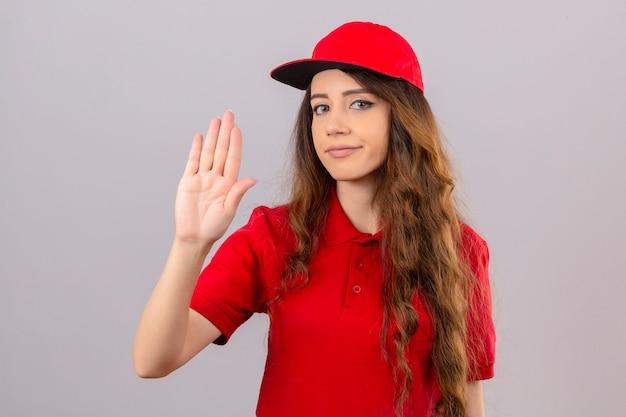 Jovem entregadora vestindo camisa pólo vermelha e boné em pé com a mão aberta, fazendo sinal de pare com gesto de defesa de expressão sério e confiante sobre fundo branco isolado