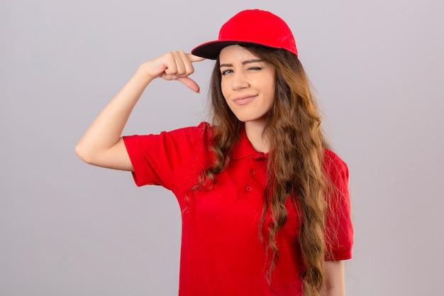 Jovem entregadora vestindo camisa pólo vermelha e boné piscando apontando para a têmpora com o dedo sobre fundo branco isolado