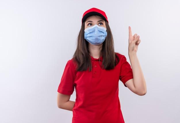Jovem entregadora vestindo camiseta vermelha com boné vermelho e máscara facial apontando para cima em fundo branco isolado