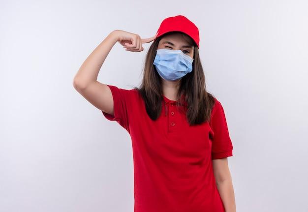 Jovem entregadora vestindo camiseta vermelha com boné vermelho e máscara facial colocou o dedo na cabeça sobre fundo branco isolado