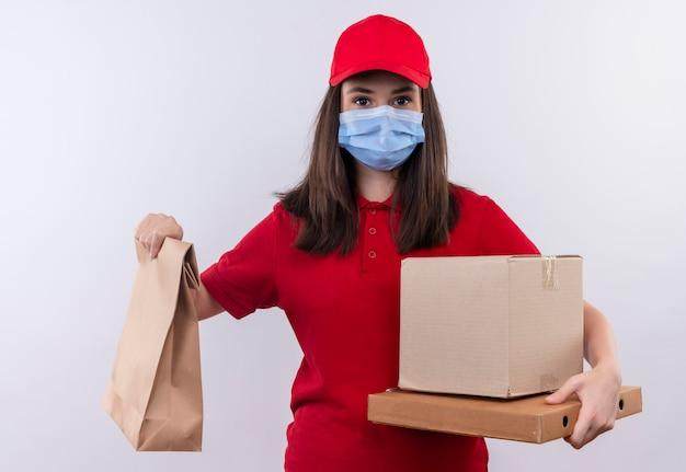 Jovem entregadora vestindo camiseta vermelha com boné vermelho e máscara facial segurando um pacote, uma caixa e uma caixa de pizza em um fundo branco isolado