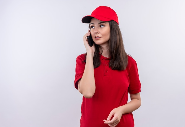 Jovem entregadora vestindo camiseta vermelha com boné vermelho fazendo uma ligação em fundo branco isolado