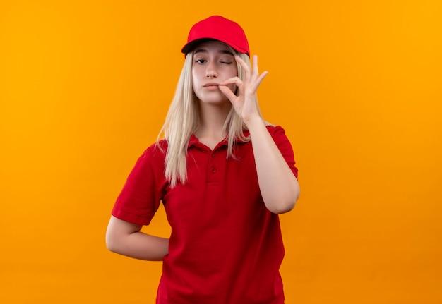 Jovem entregadora vestindo camiseta vermelha e boné mostrando um gesto delicioso na parede laranja isolada