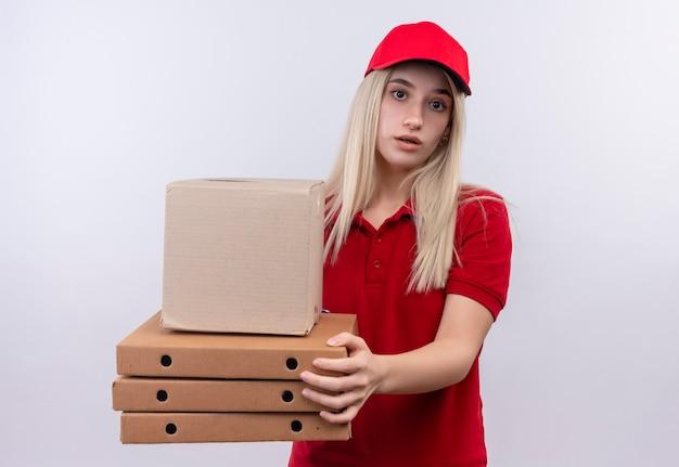 Jovem entregadora vestindo camiseta vermelha e boné segurando a caixa e a caixa de pizza na parede branca isolada