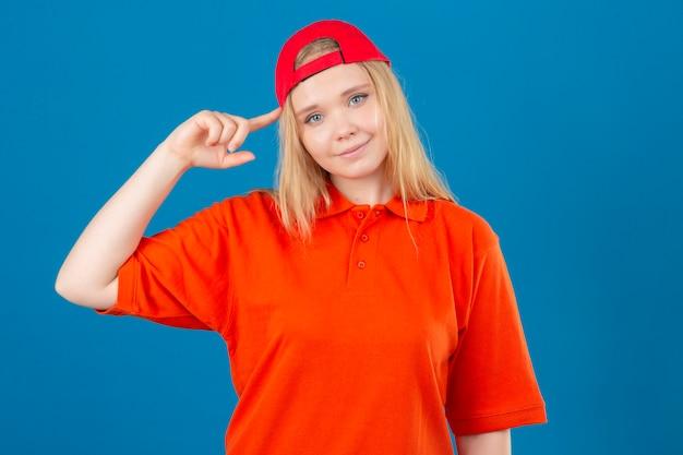 Jovem entregadora vestindo uma camisa pólo laranja e boné vermelho apontando para o templo, com o dedo pensando em uma tarefa sobre um fundo azul isolado
