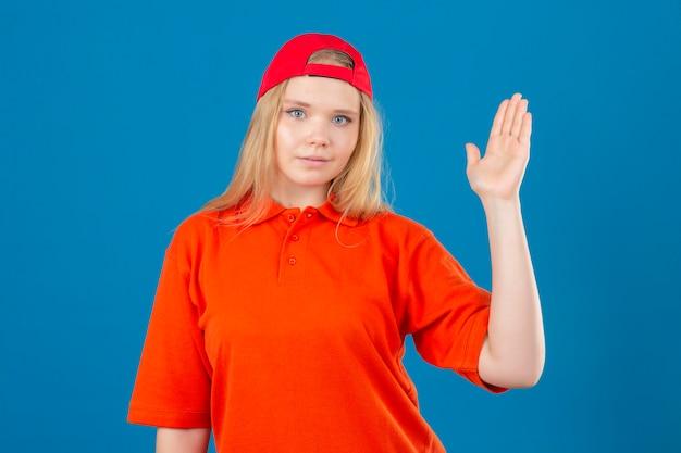 Jovem entregadora vestindo uma camisa pólo laranja e boné vermelho, sorrindo, amigável, acenando com a mão dando as boas-vindas e cumprimentando ou se despedindo sobre um fundo azul isolado
