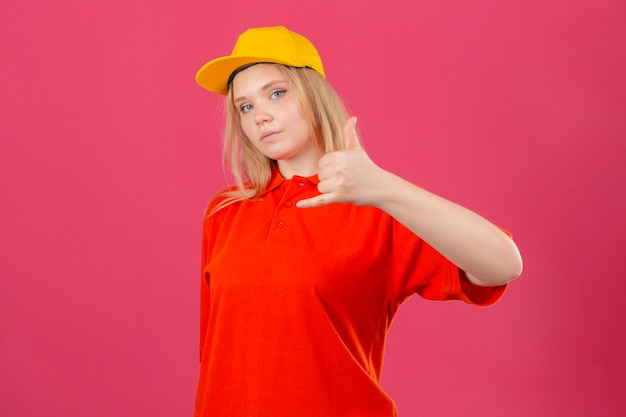 Jovem entregadora vestindo uma camisa pólo vermelha e boné amarelo, fazendo um gesto de me ligar parecendo confiante sobre um fundo rosa isolado jpg