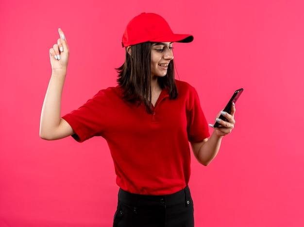 Jovem entregadora vestindo uma camisa pólo vermelha e boné olhando para a tela do smartphone mostrando o dedo indicador parecendo confiante com um sorriso no rosto em pé sobre a parede rosa