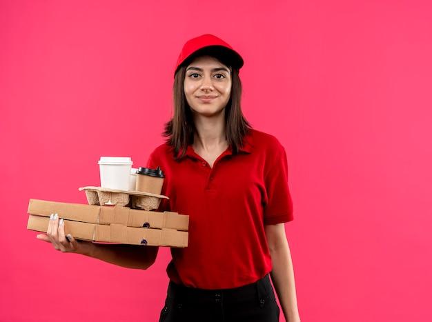 Jovem entregadora vestindo uma camisa pólo vermelha e boné segurando caixas de pizza e um pacote de comida sorrindo com uma cara feliz em pé sobre a parede rosa