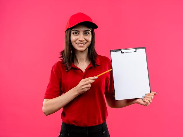 Jovem entregadora vestindo uma camisa pólo vermelha e boné segurando uma prancheta com páginas em branco apontando com lápis para ela sorrindo com uma cara feliz em pé sobre um fundo rosa