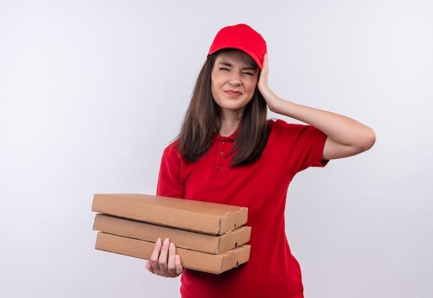 Jovem entregadora vestindo uma camiseta vermelha com boné vermelho segurando uma caixa de pizza e agarrando cabeças de ouvir em um fundo branco isolado