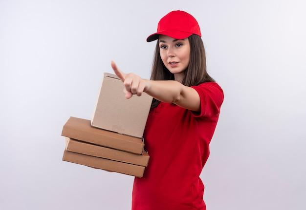Jovem entregadora vestindo uma camiseta vermelha com boné vermelho segurando uma caixa e uma caixa de pizza e aponta o dedo para o lado em um fundo branco isolado