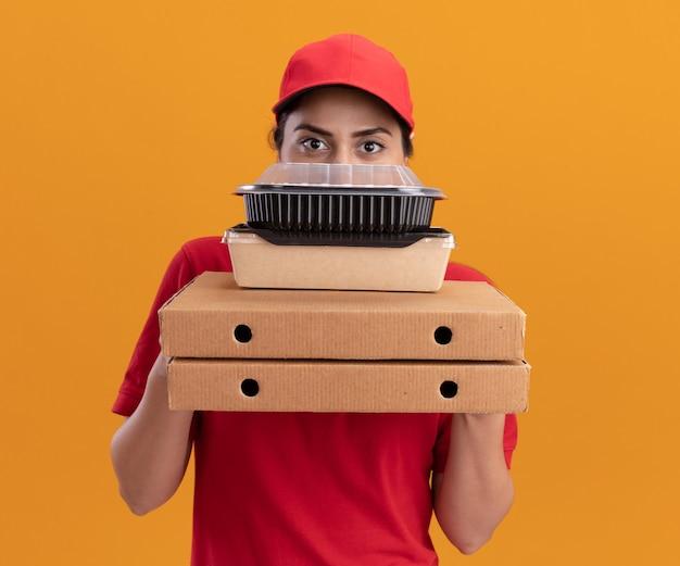 Jovem entregadora vestindo uniforme e boné coberto com caixas de pizza e recipientes de comida isolados na parede laranja