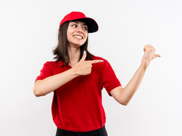 Jovem entregadora vestindo uniforme vermelho e boné apontando com os dedos para o lado sorrindo com uma carinha feliz em pé sobre um fundo branco