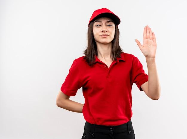 Jovem entregadora vestindo uniforme vermelho e boné olhando para a câmera com uma cara séria, fazendo sinal de pare com a mão aberta em pé sobre um fundo branco