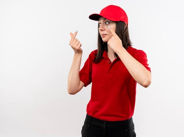 Jovem entregadora vestindo uniforme vermelho e boné olhando para o lado fazendo gesto de dinheiro esperando o pagamento em pé sobre fundo branco