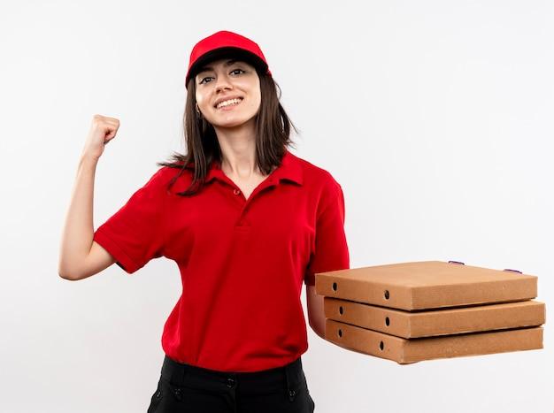 Jovem entregadora vestindo uniforme vermelho e boné segurando uma pilha de caixas de pizza cerrando os punhos, feliz e positiva, sorrindo em pé sobre um fundo branco
