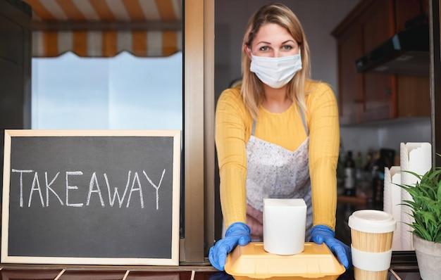 Jovem entregando comida orgânica para viagem dentro de restaurante durante confinamento por coronavírus - foco nas mãos