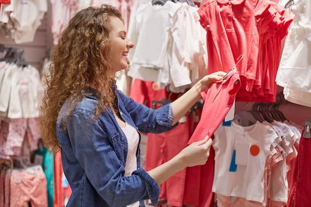Jovem entrou no departamento de crianças com roupas para crianças pequenas, se sente feliz porque viu camiseta vermelha para criança