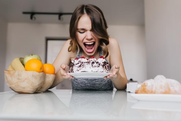 Jovem entusiasmada comendo torta cremosa. modelo feminino despreocupado, desfrutando de frutas e bolo.