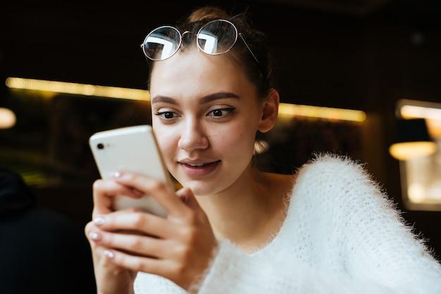 Jovem entusiasmada de óculos, sentada em um café e escrevendo uma mensagem em um smartphone