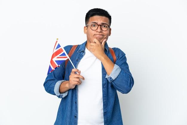 Jovem equatoriana segurando uma bandeira do reino unido, isolada no fundo branco, tendo dúvidas e pensando
