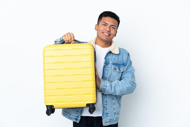 Jovem equatoriano isolado em uma parede branca de férias com uma mala de viagem