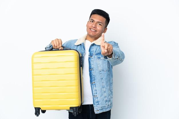Jovem equatoriano isolado no fundo branco de férias com mala de viagem e contando uma