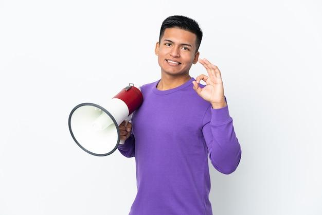 Jovem equatoriano isolado no fundo branco segurando um megafone e fazendo sinal de ok com os dedos