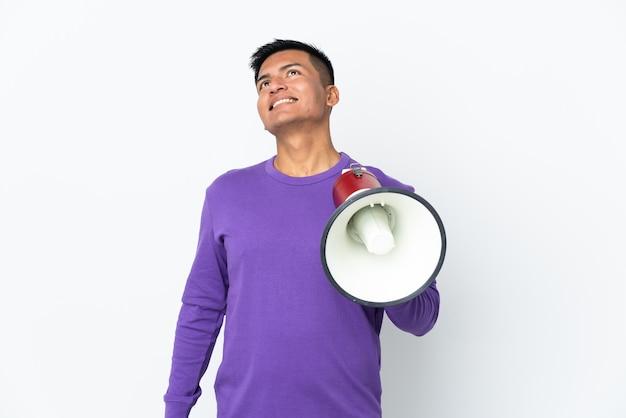 Jovem equatoriano isolado no fundo branco segurando um megafone e olhando para cima enquanto sorri
