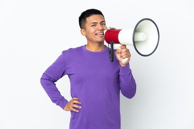 Jovem equatoriano isolado no fundo branco segurando um megafone e sorrindo