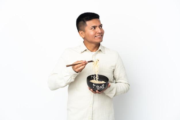 Jovem equatoriano isolado no fundo branco segurando uma tigela de macarrão com pauzinhos e olhando para cima