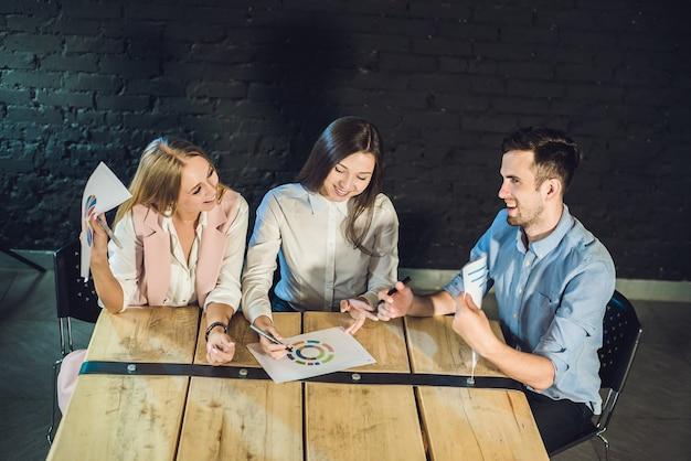Jovem equipe de colegas de trabalho fazendo uma ótima discussão de reunião no moderno escritório de coworking