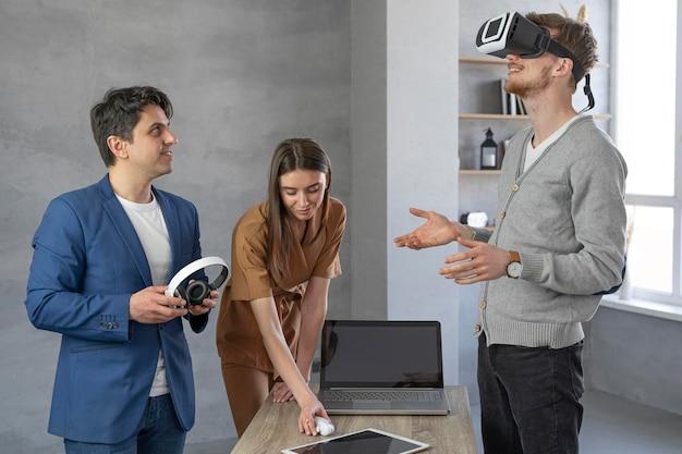 Jovem equipe de profissionais trabalhando com laptop e fone de ouvido de realidade virtual