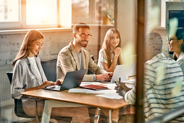 Jovem equipe profissional. grupo de jovens modernos com roupas casuais elegantes estão fazendo um brainstorming enquanto estão sentados atrás de uma parede de vidro em um escritório criativo