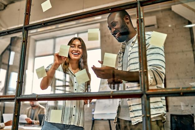 Jovem equipe profissional. mulher bonita e homem afro-americano, colando adesivos na parede de vidro no escritório criativo.