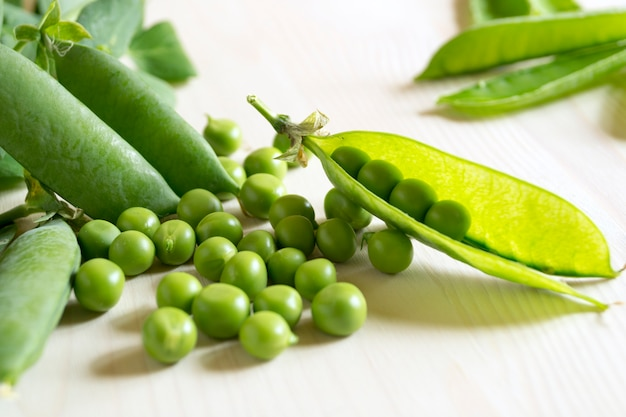 Jovem, ervilhas verdes, close-up