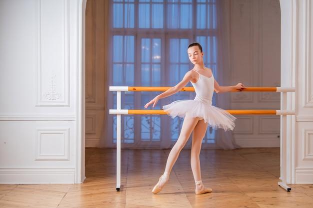 Jovem esbelta bailarina em um tutu branco fazendo sapatilhas de ponta em um bar de balé em um belo salão branco na frente de um espelho.