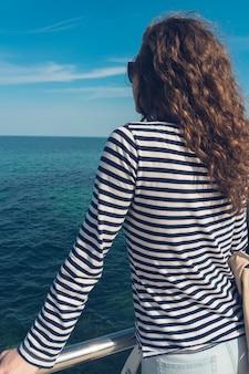 Jovem esbelta com cabelo encaracolado, olhando para o mar