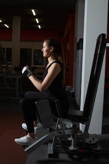 Jovem esbelta e esportiva fazendo exercícios para as pernas na academia