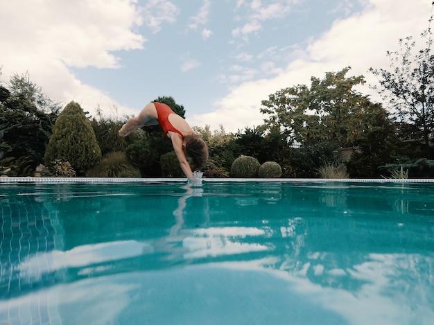 Jovem esbelta em um maiô vermelho mergulha na piscina