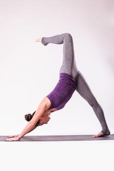 Jovem esbelta fazendo exercícios de ioga. isolado sobre fundo branco.