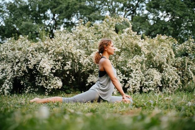 Jovem esbelta pratica esportes fazendo exercícios em pose equestre de ioga ao ar livre no parque exercícios de alongamento horizontal